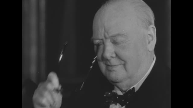 british prime minister winston churchill dons eyeglasses / churchill stands with smiling wife clementine as he reads telegrams he received regarding... - winston churchill prime minister stock videos & royalty-free footage