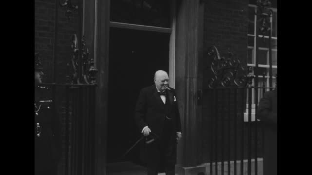 british prime minister winston churchill steps out of 10 downing street and removes hat / stands on steps for photos and puts hat back on / two cars... - prime minister stock videos & royalty-free footage