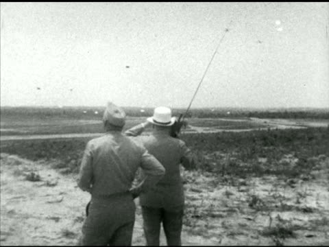 vidéos et rushes de british prime minister winston churchill w/ portable transistor radio watching us army parachute infantry paratroopers landing in field, brigadier... - infanterie