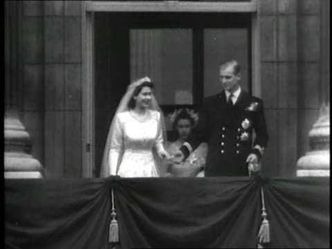 british princess elizabeth and prince philip walk out onto a balcony and wave after their wedding. - anno 1947 video stock e b–roll