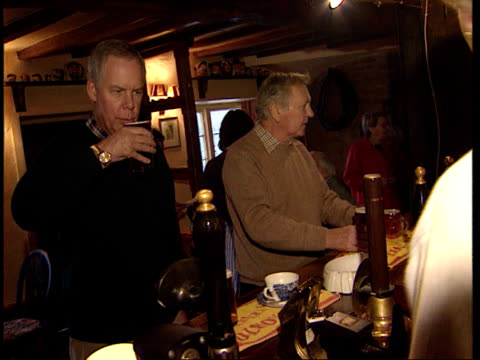 british pubs in crisis; lib england: int cms half a pint of lager tilt up placed on bar of public house man and woman drinking in pub woman drinking... - lager stock videos & royalty-free footage