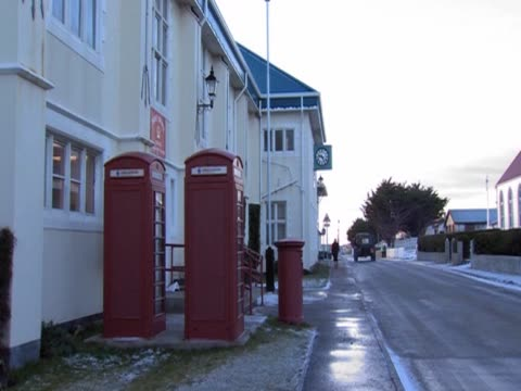 stockvideo's en b-roll-footage met british red telephone boxes stand next to a building in the falkland islands - atlantische eilanden