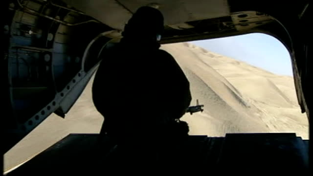 british royal marines continue to fight taliban forces; afghanistan: helmand province: sangin: int military helicopter armed british soldier seated... - 英国海兵隊点の映像素材/bロール