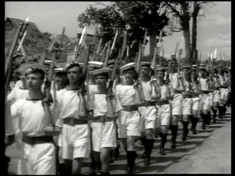 INDIA British Royal Navy troops sailors marching in warmweather white shorts uniform w/ bayonet rifles Indian dock workers moving boxes w/ hand truck...