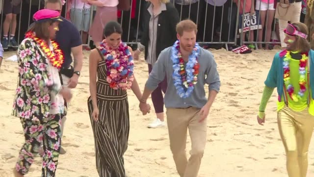 british royals harry and meghan kick off their shoes and don tropical garlands as they hit sydney's famed bondi beach for the latest stop on their... - harry meghan tour stock videos and b-roll footage