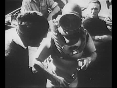 british sailors help frogman lionel crabb strap into his oxygen gear / man watches / crabb adjusts his face mask speaks to crew member at his right... - face down stock videos & royalty-free footage