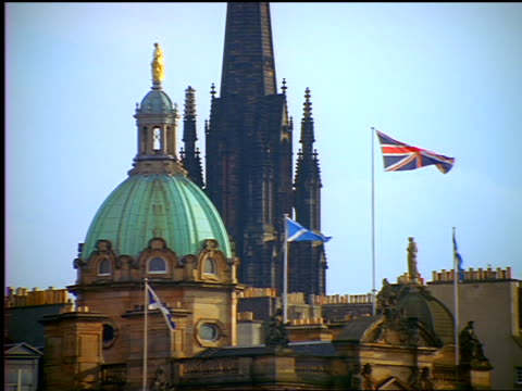 British + Scottish (Saltire) flags waving by dome + spire of St. Mary's Cathedral  / Edinburgh