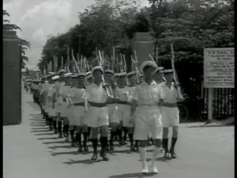 british & singaporean soldiers in warm-climate attire weapons marching out of base. war ship in ship yard. front of battle ship in yard beams... - 1942 bildbanksvideor och videomaterial från bakom kulisserna