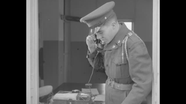 a british solder in a guard house picks up a receiver and talks on the telephone / view from the end of a striped sentry pole that is raised by a... - telephone receiver stock videos & royalty-free footage