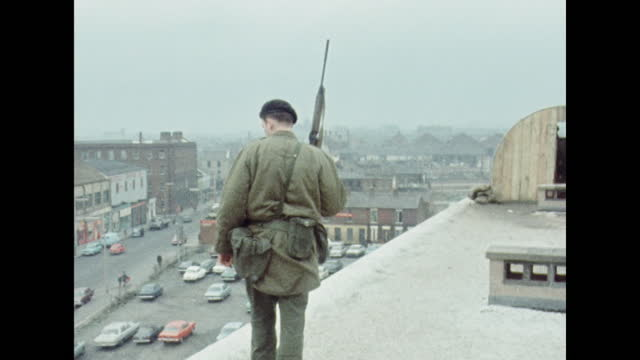 british soldier observes shankill road from rooftop, belfast; 1970. - wide shot stock videos & royalty-free footage
