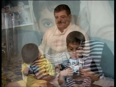 british soldiers charged with war crimes in iraq iraq int baha mousa's father sits with his two grandsons who both hold photographs of their dead... - folter stock-videos und b-roll-filmmaterial