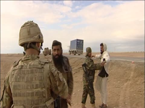 british soldiers greet members of the afghan army with a handshake whist patrolling the highway one kandahar - afghanische nationaltruppe stock-videos und b-roll-filmmaterial