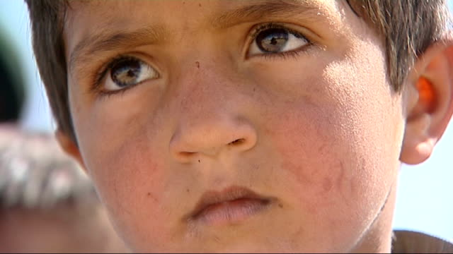 vidéos et rushes de british soldiers in musa qala; children seated outside new school close shots of faces of children school governor addressing school community sot - afghanistan