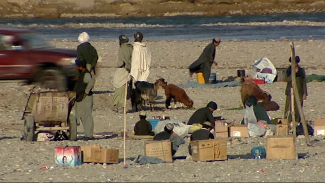 british soldiers in musa qala long shot of afghan people and vehicles beside winding river afghan men with boxes and animals beside river men on foot... - push cart stock videos and b-roll footage
