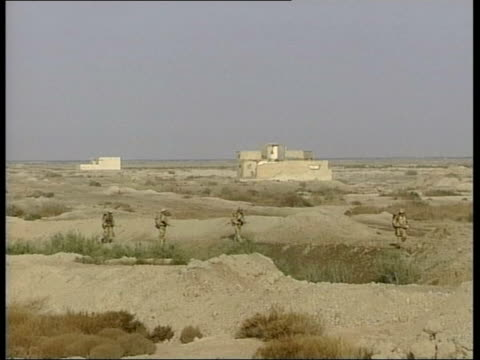 british soldiers killed and injured in separate attacks lib nr alamara british paras advancing thru scrubland - 2003 stock-videos und b-roll-filmmaterial