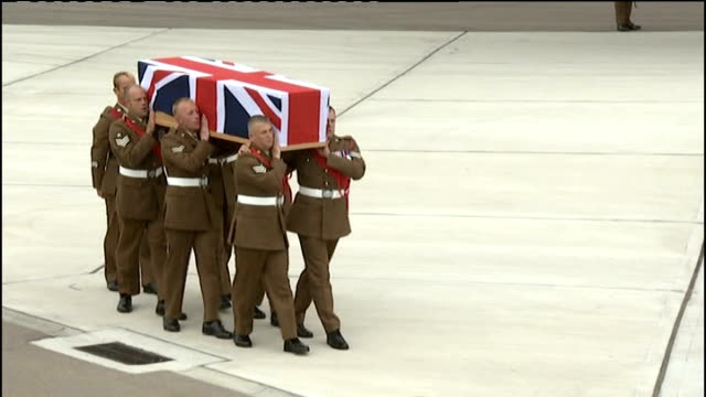 stockvideo's en b-roll-footage met british soldiers killed in afghanistan repatriated; union jack draped coffin carrying body of sergeant gareth thursby carried along tarmac by... - repatriëring