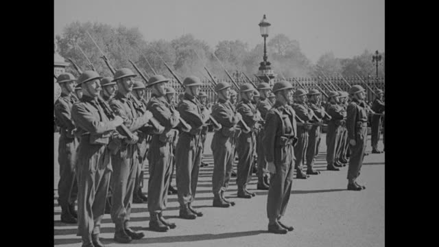stockvideo's en b-roll-footage met british soldiers march in formation through gate onto grounds of buckingham palace as part of military review during world war ii / soldiers present... - british military