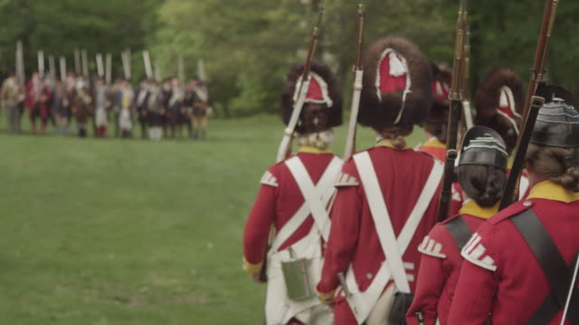 british soldiers march toward a line of colonial soldiers during a reenactment of a revolutionary war battle. - infantry stock videos & royalty-free footage