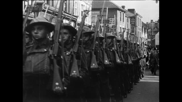 montage british soldiers marching down a city street and children walking down war-torn streets surrounded by rubble / oxford, england, united kingdom - 1946年点の映像素材/bロール