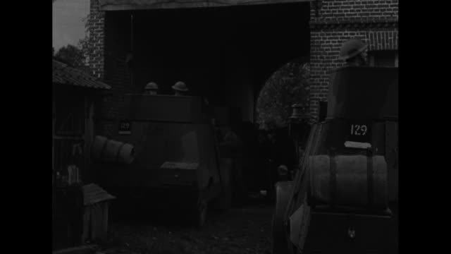 vídeos de stock, filmes e b-roll de vs british soldiers of the british expeditionary force run from billet to armored vehicles and drive from courtyard onto country road / note exact... - carro blindado