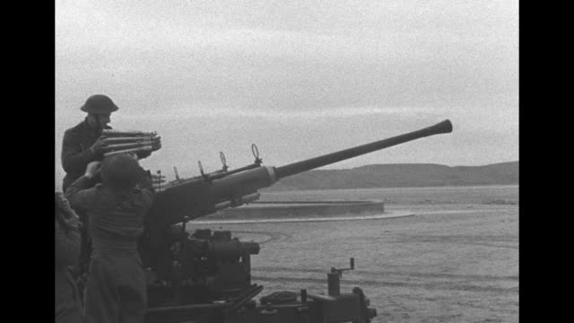 vs british soldiers on beach with bofors 40 mm guns / airplane flying far away / vs men loading and firing the 40 mm guns with pan to civilians... - mm stock videos and b-roll footage