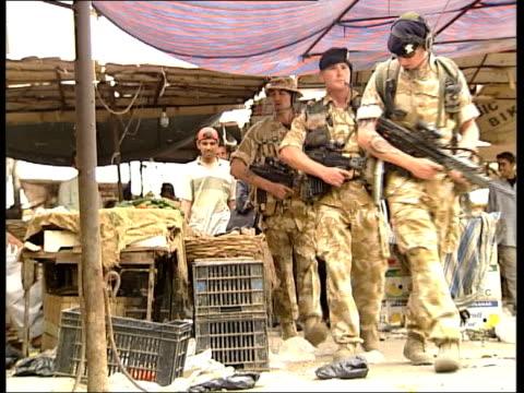 vídeos de stock, filmes e b-roll de lib british soldiers patrolling thru market wearing berets and floppy hats rather than helmets cbv ditto track la cbv ditto track - fallujah