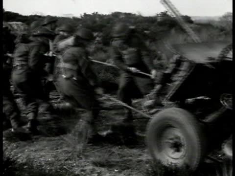 British soldiers pulling antitank gun up small hill WS Firing antitank gun WWII
