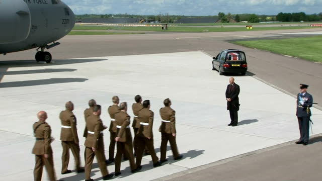 stockvideo's en b-roll-footage met british soldiers repatriation; coffin placed in hearse and driven away / fifth coffin carried from plane draped in union jack flag - repatriëring