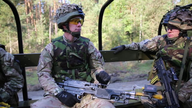 british soldiers ride in the back of a truck while training in for a roadside ambush of a vehicle convoy during the 2014 nato rapid trident training... - ambush stock videos and b-roll footage