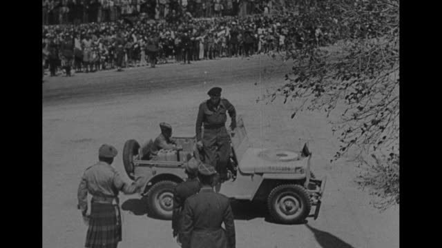 vídeos de stock, filmes e b-roll de british soldiers walking along both sides of road / cars driving down street of town / shot from moving vehicle of crowd of tunisian townspeople on... - forças aliadas