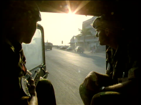 British soldiers working as United Nations Peace Keeping Forces look out to deserted streets from back of jeep as sun beams flare. Angola.