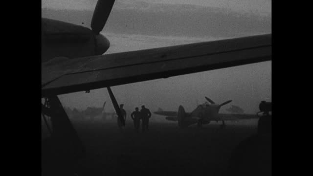 stockvideo's en b-roll-footage met british spitfire with markings wz star a / pilots and ground man looking left / airplanes in sky under low clouds / silhouetted men airplane seen... - 1942