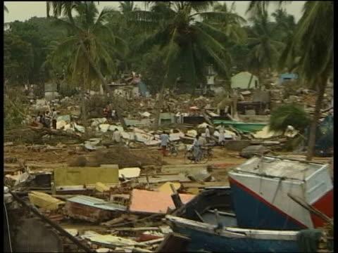 stockvideo's en b-roll-footage met british sri lankans grieving relatives tx sri lanka hambantota wreckage strewn over village - 2004