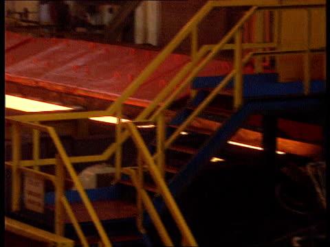 vidéos et rushes de british steel; scotland ravenscraig steelworks seq red-hot strip of steel along conveyor belt & being rolled - acier
