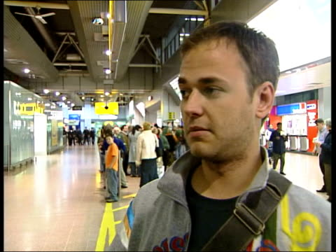 British survivors continue to return home INT BA006C flight from Bangkok on arrivals information display screen Charlie Anderson interviewed SOT...