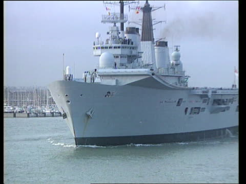 british task force heads for adriatic; england: hants: portsmouth: ext bow of hms ark royal in water pull out as ship towards out of harbour: crew... - bosnia and hercegovina stock videos & royalty-free footage