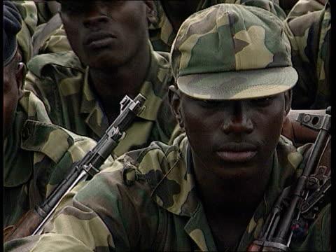 british tourists kidnapped by rwandan rebels; lib rwanda: ext rwandan troops gathered with hills in b/g lib civilians searched by troops lib uganda:... - kampala stock videos & royalty-free footage