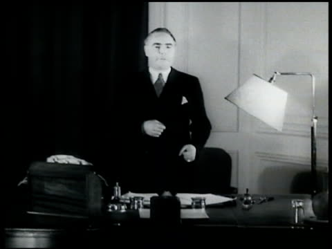 vídeos de stock e filmes b-roll de british transport minister leslie horebelisha standing behind desk saying wives should tell husbands to be careful come home alive - 1935