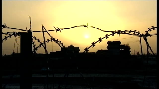 British troops deployed in Lashkar Gar and their reaction to Prince Harry leaving DUSK British base and barbed wire fence silhouetted against setting...