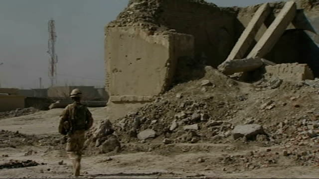 british troops help to rebuild musa qala; soldiers patrolling near damaged buildings and piles of rubble damaged wall man with wheelbarrow and... - rebuilding stock videos & royalty-free footage