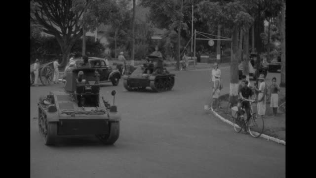 british troops ride through rain-slicked streets in java after arriving via ship / vs halftracks and small tanks ride on picturesque streets /... - malaysian ethnicity stock videos & royalty-free footage