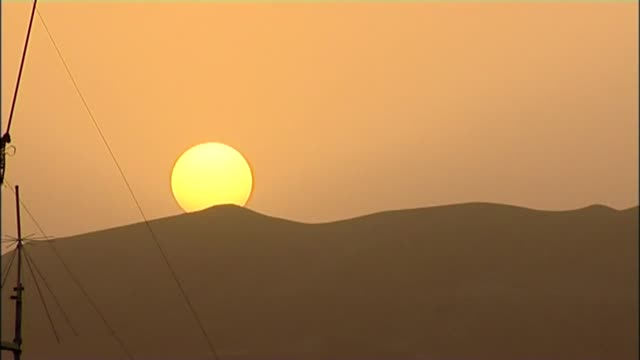 british troops sent to sangin to help fight taliban; lib / tx 20.9.2010 afghanistan: helmand province: sangin: ext sun setting behind mountain low... - 飾り板点の映像素材/bロール