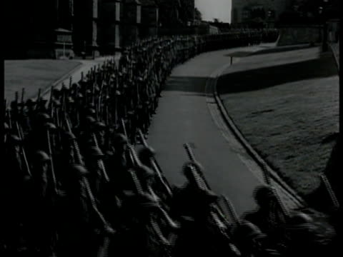 british troops w/ rifle & gear marching down curvy street. reporters correspondents on hill w/ camera equipment. bomber air planes in-flight overhead. - 1939 stock videos & royalty-free footage