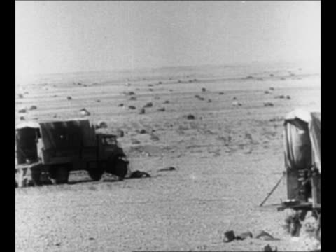 british trucks in egyptian desert during world war ii / soldiers set up anti-aircraft guns / soldier stacks bombs under camouflage net / soldier with... - britisches militär stock-videos und b-roll-filmmaterial