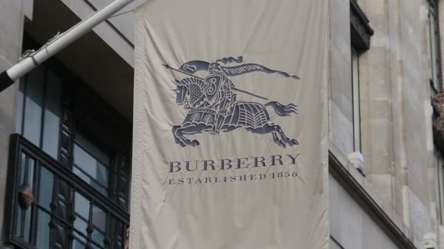 vidéos et rushes de a british union flag right flies beyond the burberry group plc flag outside the company's luxury clothing store on regent street in london uk on... - burberry