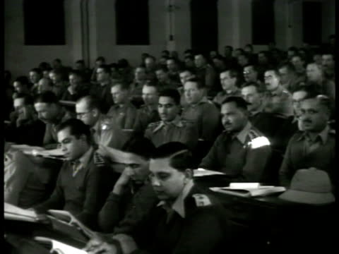 british war college class in india auditorium british & indian soldiers sitting w/ paperwork. japanese war supplies report cover. british officers... - 植民地様式点の映像素材/bロール