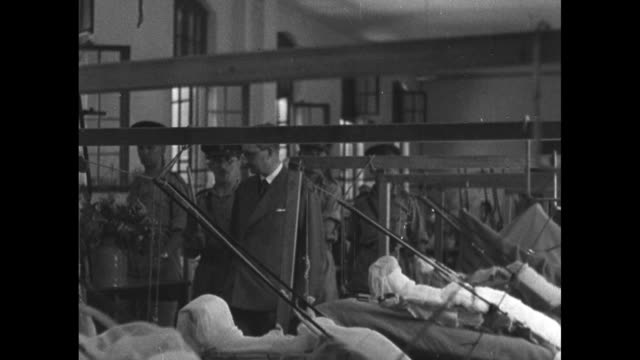 vidéos et rushes de british war secretary sir james grigg, accompanied by officers, walks along aisle in tripoli military hospital ward, wounded soldiers standing beside... - british military