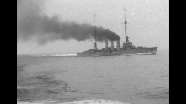 WS British warship moves swiftly through water with black smoke emitting from its smokestacks / ship's personnel and officials stand on deck of...