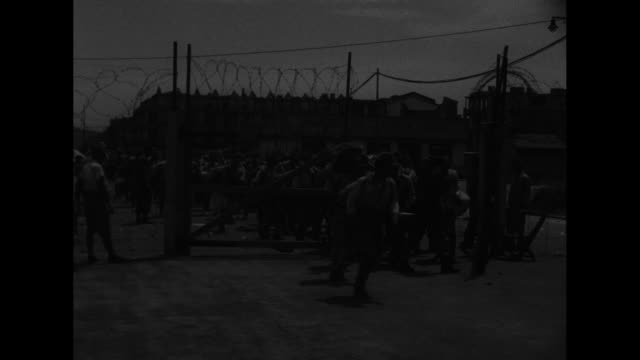 BritishIndian guards walk before rows of Japanese prisoners / individual faces of the prisoners and an officer / prisoners with heavy backpacks trot...