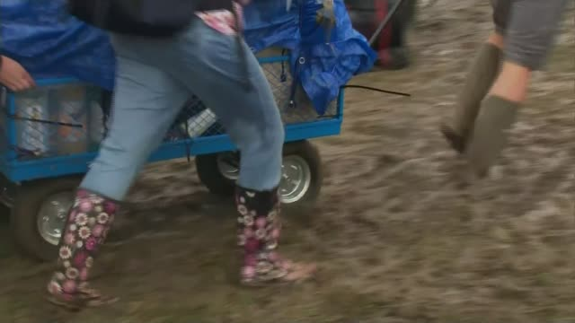 stockvideo's en b-roll-footage met britons head to the seaside on the hottest day of the year so far; lib glastonbury: festival goers pulling cart along through mud - festivalganger